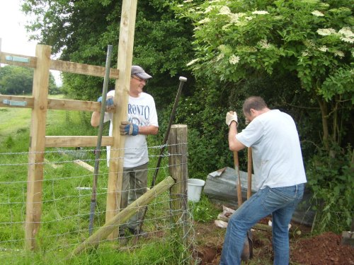 Keith leaning on the new stile while Neil works hard!